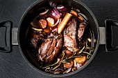 Leg of lamb in red wine with onions, carrots and rosemary