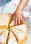 Kinderhand greift nach einem Stück Victoria Sponge Cake