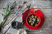 Fried Japanese turnips with leaves and seeds in a red bowl