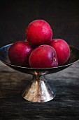 Fresh red plums in an antique metal bowl