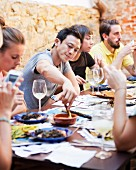 Mann asiatischer Herkunf dippt Lauch in Romesco