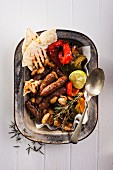 Sausages with roasted vegetables and unleavened bread