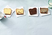 Four different slices of Madeira cake on napkins