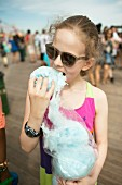 A little girl eating candy floss at a festival