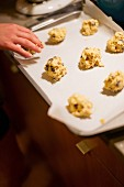 Balls of cookie dough being placed on baking tray