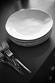 A stack of white plate and a pirate forks on grey table