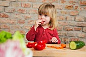 A little blonde girl in a kitchen eating raw vegetables