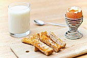A boiled egg and strips of French toast with a glass of milk