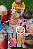 A view of young children eating spaghetti at picnic table in a garden
