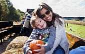 A mother and a son sitting in a tractor trailer holding a pumpkin