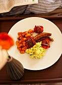 An English breakfast with scrambled eggs, baked beans, tomatoes, bacon and sausages