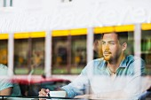 A young man looking through a cafe window