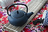 A black oriental teapot seen from above