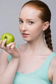 A portrait of young woman holding a green apple