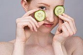 A portrait of a young woman with two slices of cucumber as an eye mask