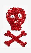 Totenkopf und gekreuzte Knochen-Symbol mit roten Bonbons erstellt