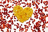 A heart made from yellow bonbons surrounded by red and orange bonbons