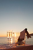 A bottle of champagne in a cooler and two filled glasses against a sunset over the sea