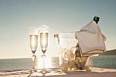 A bottle of champagne in a chiller and two glasses of champagne with a view of a sunset by the sea