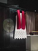 Elegantes Abendkleid und Schal auf Kleiderbügel an Schrank hängend