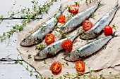 Fresh, raw sardines seasoned with salt and thyme with halved cherry tomatoes