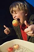 A little boy holding an apple between his teeth