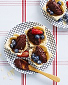Pastry dishes filled with dark chocolate mousse, fresh strawberries and blueberries