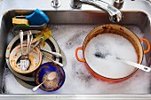 A kitchen sink full of dirty dishes and water