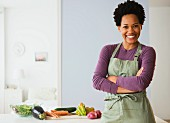 A young black woman in a kitchen with vegetables
