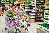 A young couple in a supermarket trolley dash