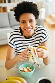 A black woman slicing a banana into a bowl of muesli for breakfast