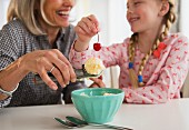 A grandma and her granddaughter making an ice cream dessert