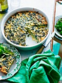Chard frittata with feta cheese in a baking dish with a slice on a plate