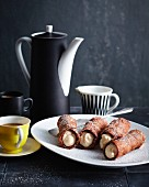 Dark ricotta cannoli on a plate with a jug of coffee