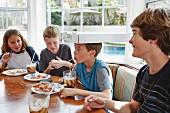 Jungs essen Pizza und trinken Cola in Küche, einer balanciert Pizzaschachtel auf dem Kopf