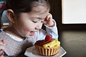 A little girl with a fruit tartlet