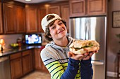 A teenage boy in a kitchen holding a large sandwich