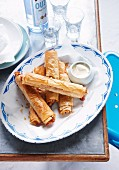 Stuffed puff pastry rolls served with ouzo and aioli (Greece)