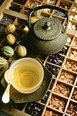 Grüner Tee in einer Teeschale auf großer Kräuter- und Gewürzesammlung