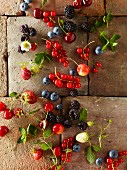 Fresh berries and cherries on a tiled floor