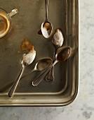 Kaffee und Löffel mit Resten von Milchschaum auf Metalltablett