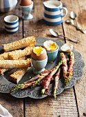 Soft-boiled eggs, asparagus with prosciutto and strips of white bread