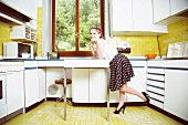 A young woman in a vintage kitchen wearing 1950s style clothing