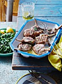 Lamb chops with lemon and mint in a ceramic dish