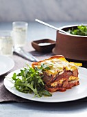 A portion of veal and pork lasagne with a rocket salad