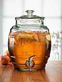 Apple spritzer in a glass barrel with a tap