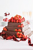 A square strawberry cake with chocolate glaze