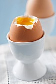Soft-boiled eggs, one decapitated and one whole