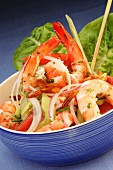 Exotic prawn salad with vegetables in a blue bowl