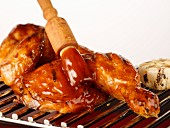Grilled chicken being brushed with barbecue sauce